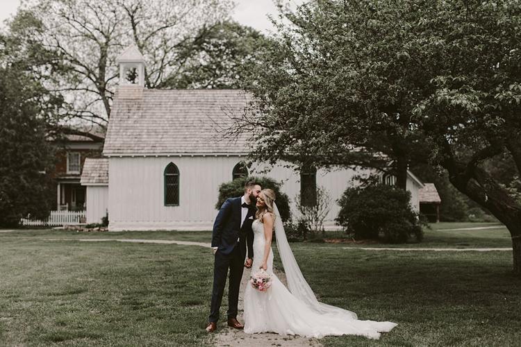 Couple kiss outside of chapel at Balls Falls