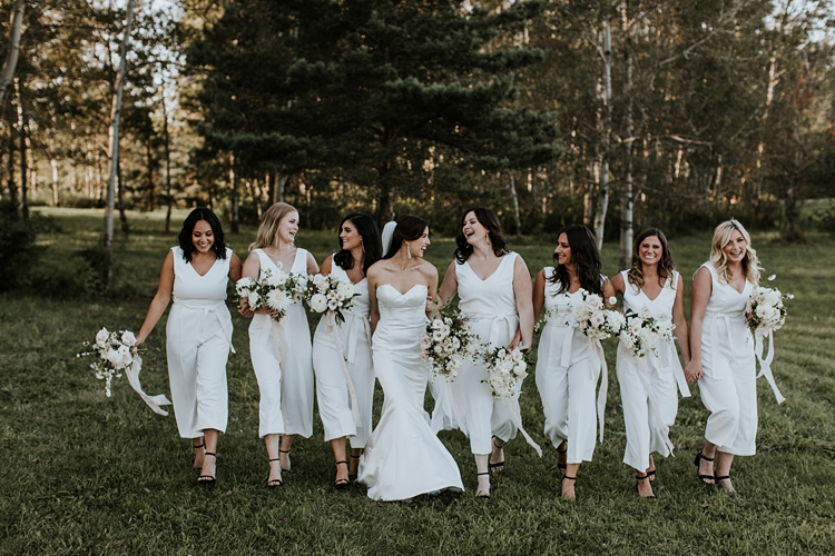 Bride and bridesmaids walking through forest wearing all white