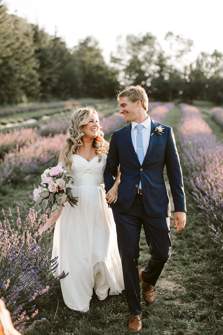 Couple walk through lavender field on their wedding day