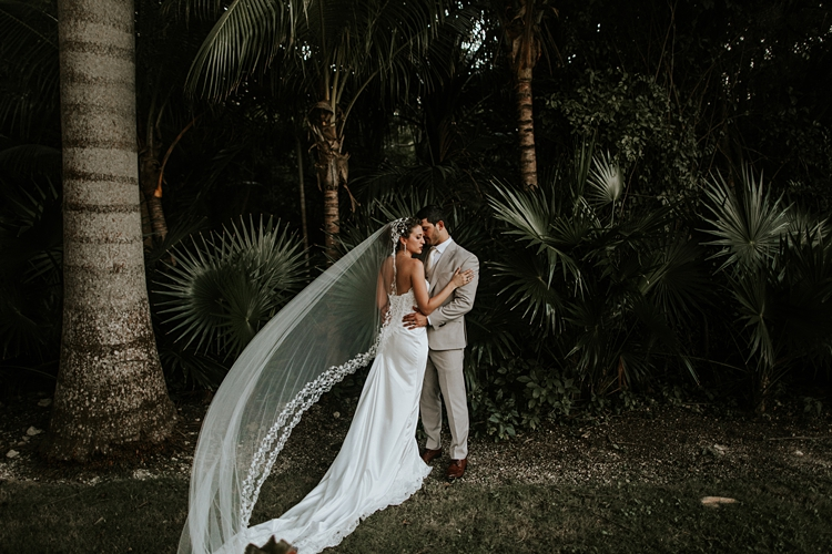 Bride and groom kissing by palm trees at Grand Palladium Mexico